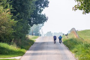 An Amish couple enjoys a bike ride on a country road.