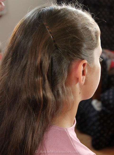 When finished, Christina's hair is pulled back behind her ears, ready for a ponytail.