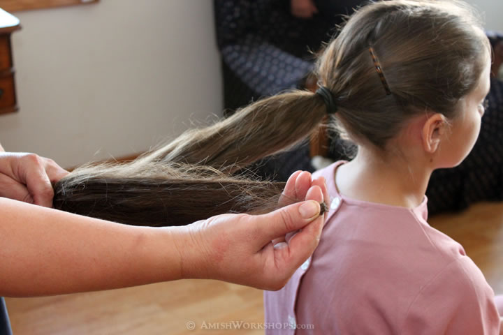 In order to fit the Amish girl's hair under a prayer kapp, the ponytail must first be folded into a bun.