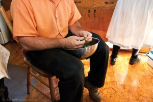 An Amish man helps his wife in the kitchen by shelling peas.