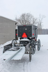 An Amish buggy pulling a wagon on a snowy day.