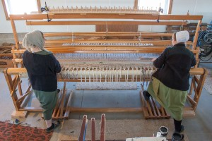 Amish weavers working together at a large loom.