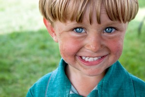 A young Amish boy flashes a winning smile on a warm summer day.