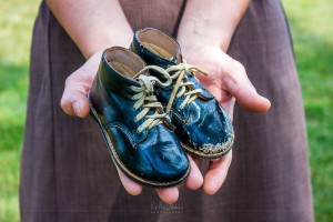 An Amish woman shows off her grandfather's baby shoes.