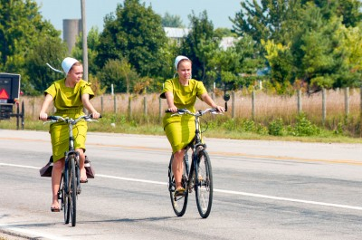 Teenaged Amish girls riding bicycles in Indiana.