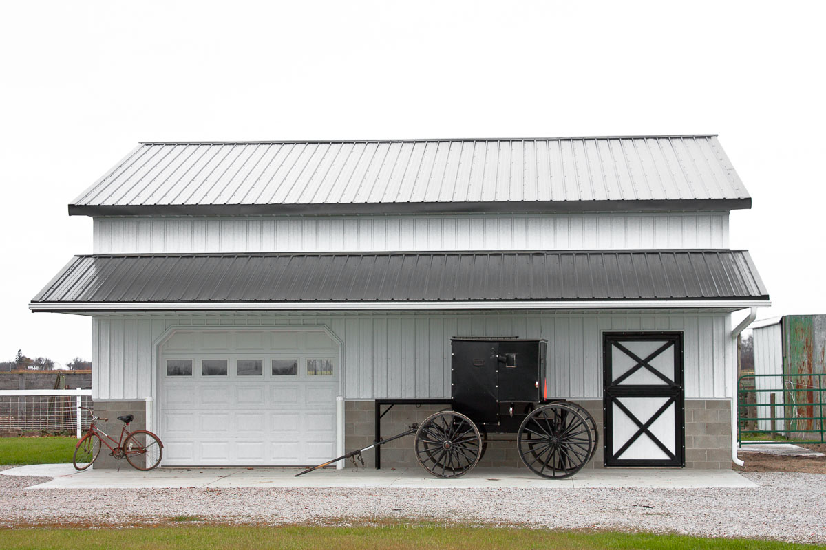 A bike and Amish buggy parked outside a barn.