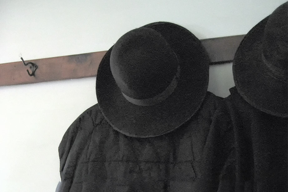 Amish man's hat and vest hanging on a hook.